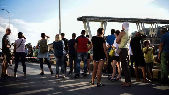 People stand looking at the Morandi motorway bridge.