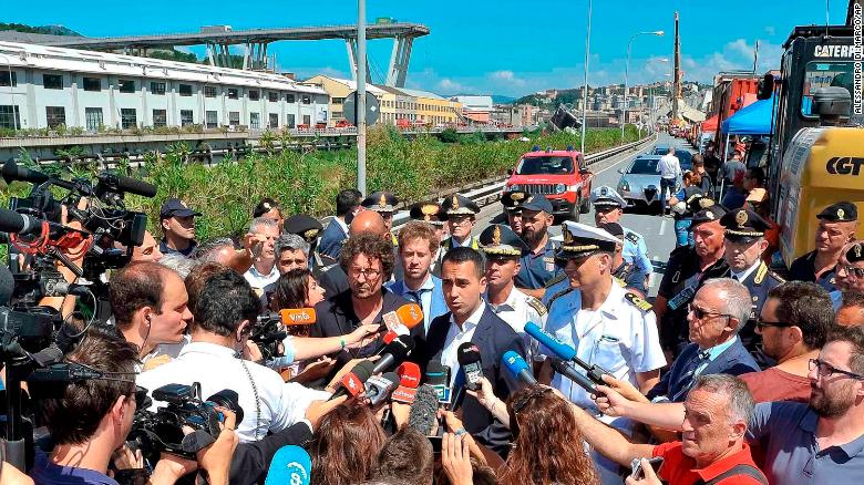 Luigi Di Maio (center right) and the transport and infrastructure minister Danilo Toninelli (center left with glasses) speak to the media in front of the collapsed bridge on Wednesday.