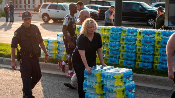 Emergency response teams hand out bottled water to residents at Parchment High School.