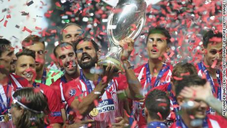 Diego Costa of Atletico Madrid celebrates with the trophy following his team's UEFA Super Cup victory over Real Madrid.
