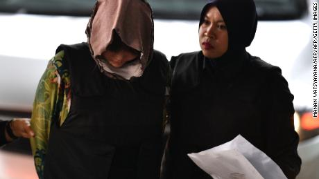 Doan Thi Huong (left) is escorted by Malaysian police to court on Thursday, August 16.