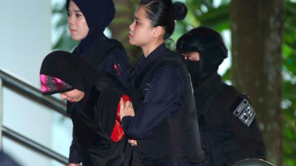 Siti Aisyah, left, is escorted by police as she arrives for Thursday