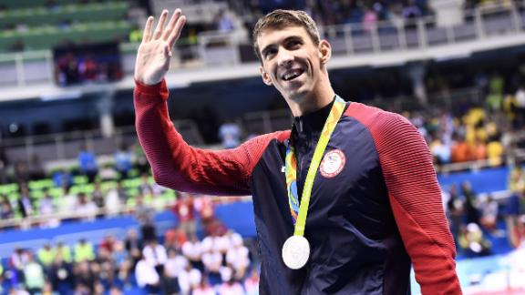 Silver medallist USA's Michael Phelps waves during the medal ceremony of the Men's 100m Butterfly Final during the swimming event at the Rio 2016 Olympic Games at the Olympic Aquatics Stadium in Rio de Janeiro on August 12, 2016.   / AFP PHOTO / CHRISTOPHE SIMON        (Photo credit should read CHRISTOPHE SIMON/AFP/Getty Images)