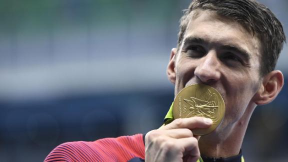 Michael Phelps celebrates with his gold medal during the podium ceremony for the Men's 4x200m Freestyle Relay Final at the 2016 Olympics.