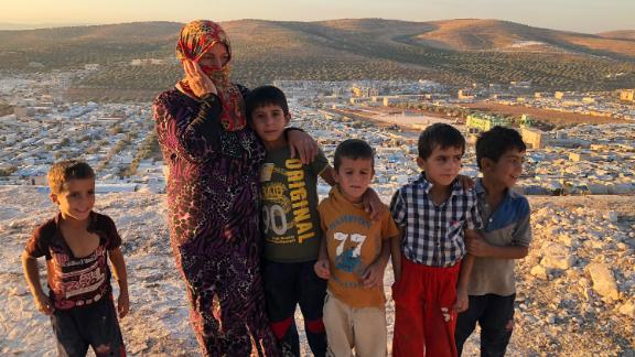 "Vaciha Turki Al Omar, 30, has been in Idlib for seven months. She on the hill overlooking the sprawling refugee camp with her kids. ""We can try to fight but the kids are our weakness so we must run away,"" she says."