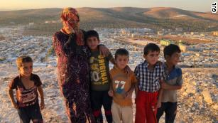 "Vaciha Turki Al Omar, 30, has been in Idlib for seven months. She on the hill overlooking the sprawling refugee camp with her kids. ""We can try to fight, but the kids are our weakness so we must run away,"" she says."