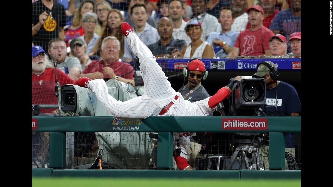Carlos Santana of the Philadelphia Phillies falls into a camera while attempting to catch a foul ball during a baseball game against the Boston Red Sox on Tuesday, August 14, in Philadelphia, Pennsylvania. The Red Sox won 2-1.