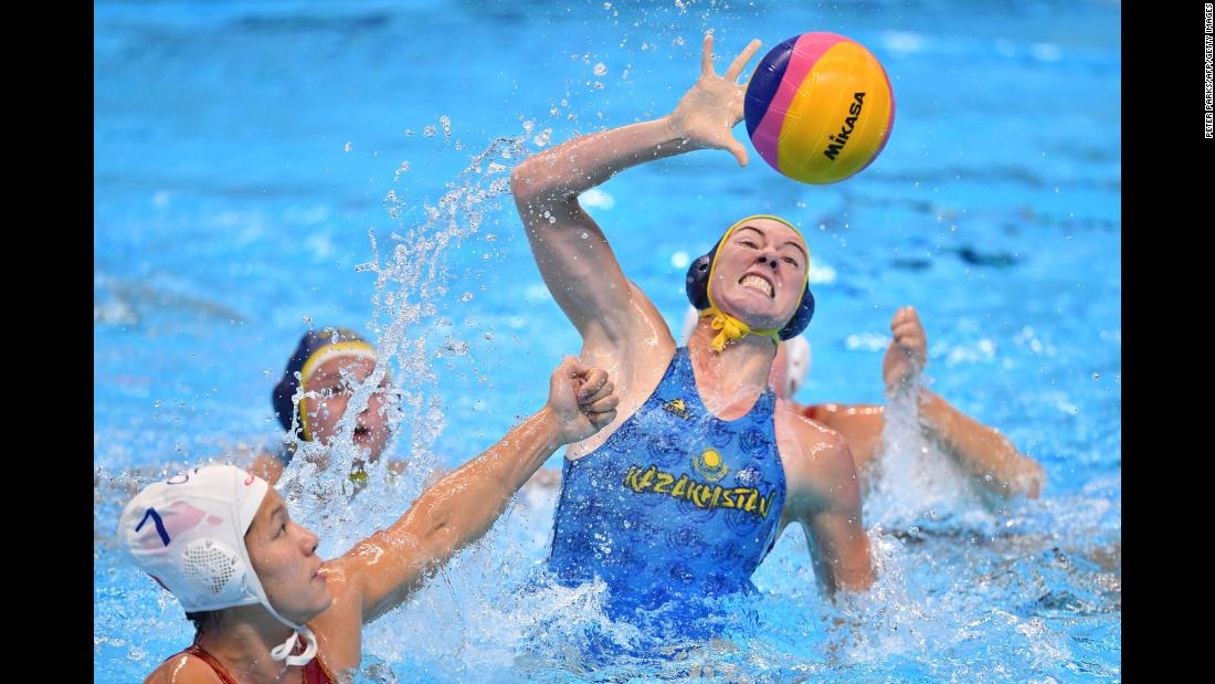 China's Nong Sanfeng, left, has a shot blocked by Uzbekistan's Anna Turova during a water polo match at the Asian Games in Jakarta, Indonesia, on Thursday, August 16.