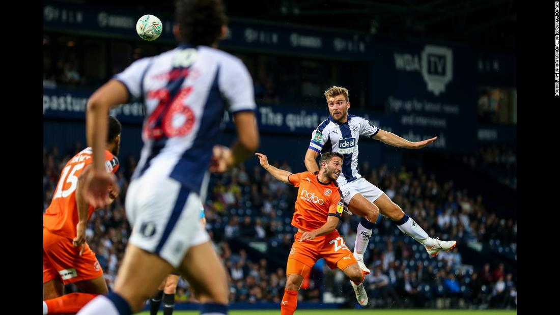 James Morrison of West Bromwich Albion jumps over Luke Gambin of Luton Town for a header during a Carabao Cup match on Tuesday, August 14, in West Bromwich, England.