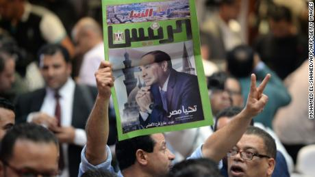 An Egyptian man carries a copy of a newspaper, bearing the portrait of Egyptian President Abdel Fattah el-Sisi in Cairo on April 2, 2018.