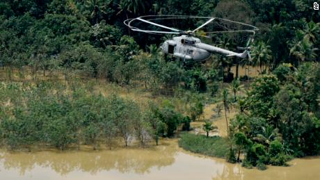 An Indian air-force helicopter on rescue mission flies through a flooded area in Chengannur in the southern state of Kerala on August 19.