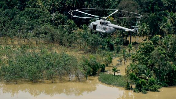 An Indian air-force helicopter on rescue mission flies through a flooded area in Chengannur in the southern state of Kerala, India, Sunday, August 19.
