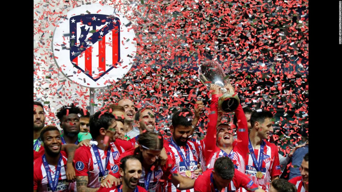 Atlético Madrid's Antoine Griezmann holds up the trophy after his team won the Super Cup on Wednesday, August 15. Atlético Madrid beat Real Madrid 4-2.