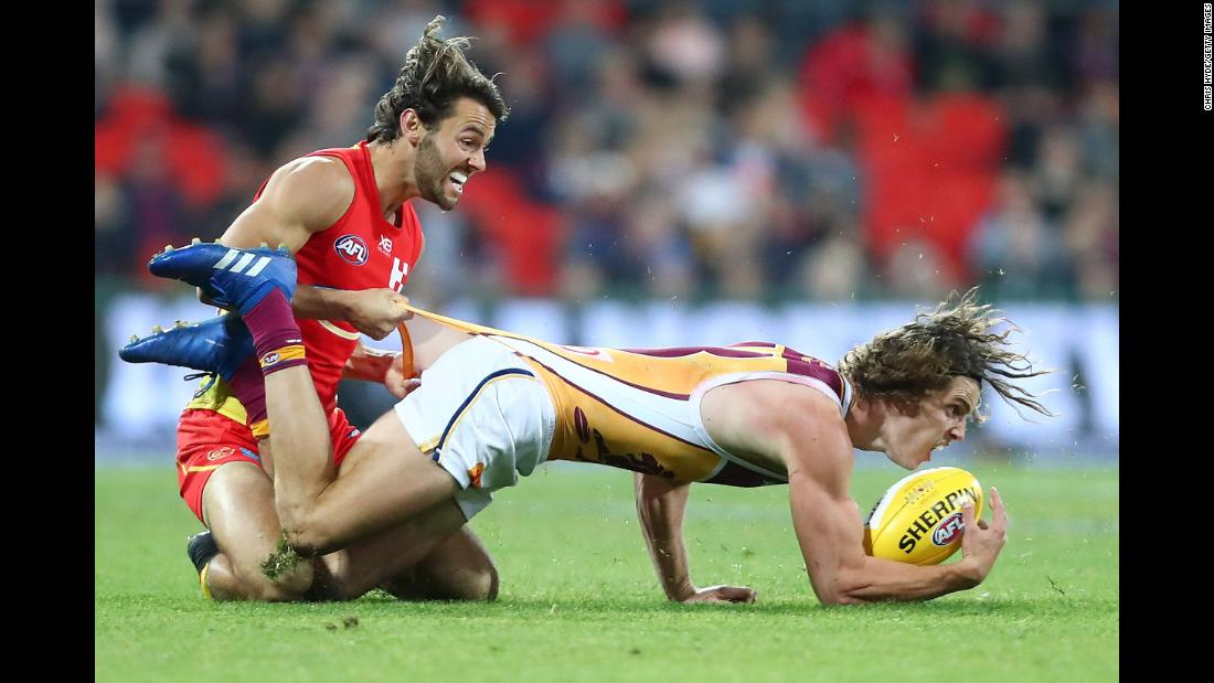 Jarrod Berry of the Brisbane Lions is tackled by Lachie Weller of the Gold Coast Suns during an Australian Football League match on Saturday, August 18, in Gold Coast, Australia.