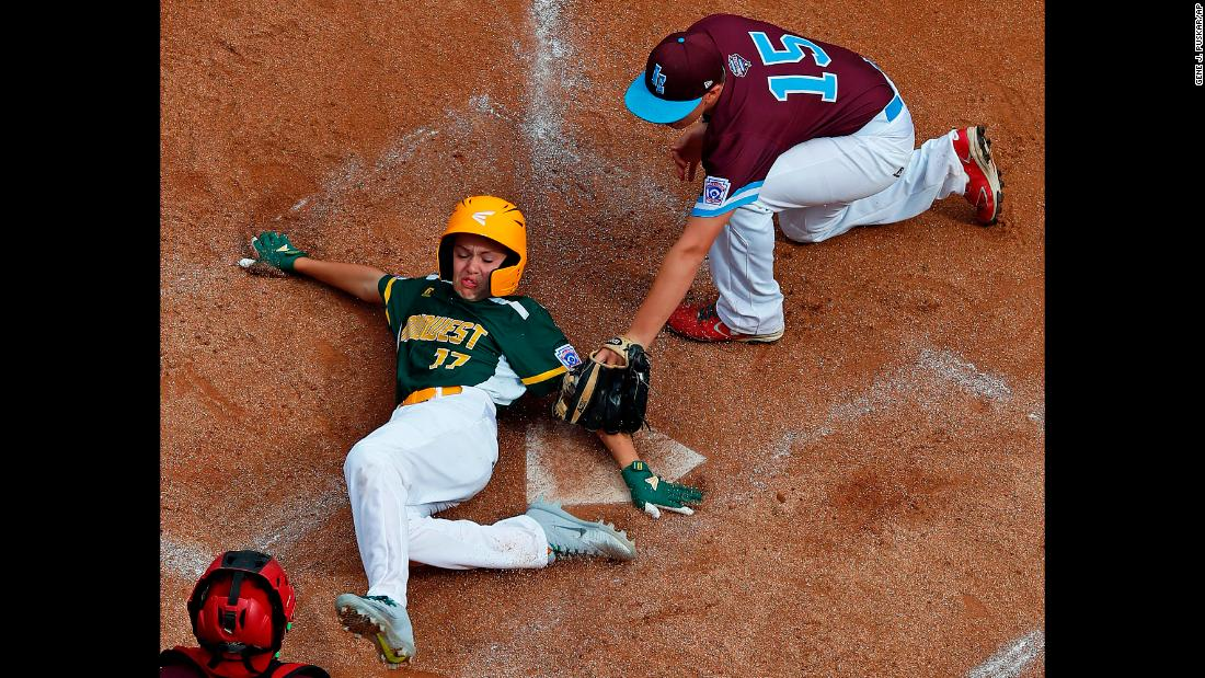 Alex Stewart of Des Moines, Iowa, scores under the tag by Logan Lama of Coventry, Rhode Island, in the fourth inning of a Little League World Series tournament game in South Williamsport, Pennsylvania, on Saturday, August 18. Upon review, the umpire's safe call was upheld.