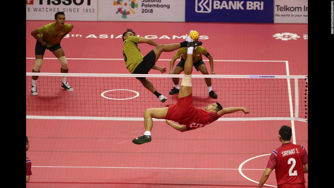 Thailand's Pornchai Kaokaew spikes the ball as Malaysia's Mohamad Azlan Alias attempts to block during a preliminary round Sepak Takraw match at the Asian Games in Jakarta, Indonesia, on Sunday, August 19.