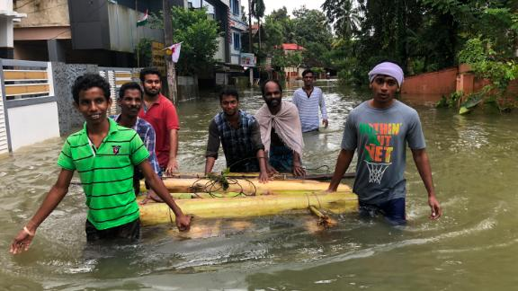 Young boys pull a makeshift raft made of banana trees through filthy flood water to rescue people in Peringara, Kerala, India.