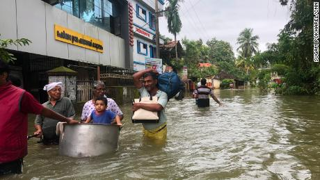 Victims of the floods wade through waist-deep water in Kerala.