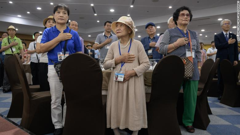 South Korean participants of the inter-Korean family reunions stand for the national anthem as they undergo a briefing on the eve of the departure for North Korea, at a hotel resort in Sokcho on August 19, 2018.