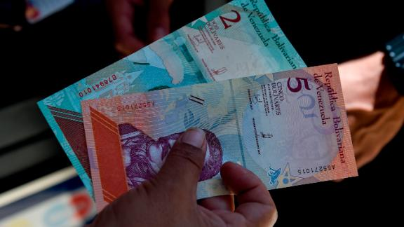 A man shows new five Bolivar-notes in Caracas on August 20, 2018. - Caracas is issuing new banknotes after lopping five zeroes off the crippled bolivar, casting a pall of uncertainty over businesses and consumers across the country. (Photo by Federico PARRA / AFP)        (Photo credit should read FEDERICO PARRA/AFP/Getty Images)