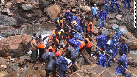 Indian Army personnel and Kerala state police work to build a temporary bridge over a rocky river following heavy flooding in Nelliyampathy in Palakkad district of Kerala.