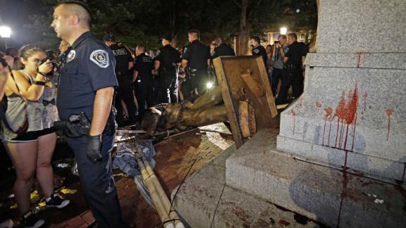 Police stand guard after the confederate statue known as Silent Sam was toppled by protesters.