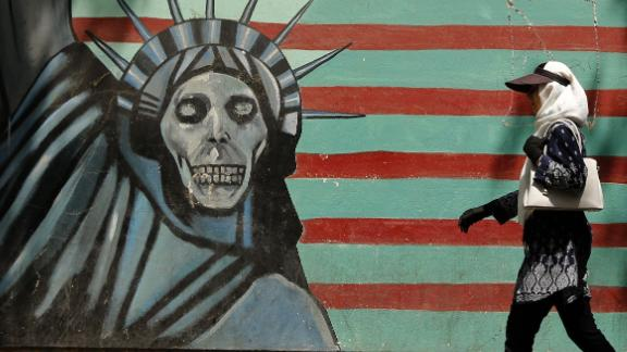 "An Iranian woman walks past a mural depicting the Statue of Liberty with a dead face, painted on the wall of the former US embassy in the capital Tehran on August 7, 2018 - US President Donald Trump warned countries against doing business with Iran today as he hailed the ""most biting sanctions ever imposed"", triggering a mix of anger, fear and defiance in Tehran. (Photo by ATTA KENARE / AFP)        (Photo credit should read ATTA KENARE/AFP/Getty Images)"