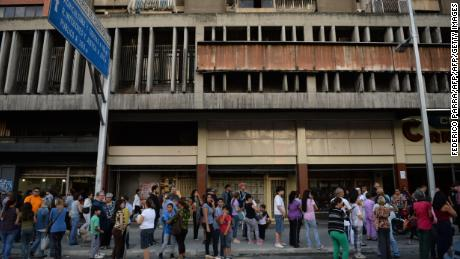 People wait in the streets after evacuating buildings in Caracas on August 21 following an earthquake.