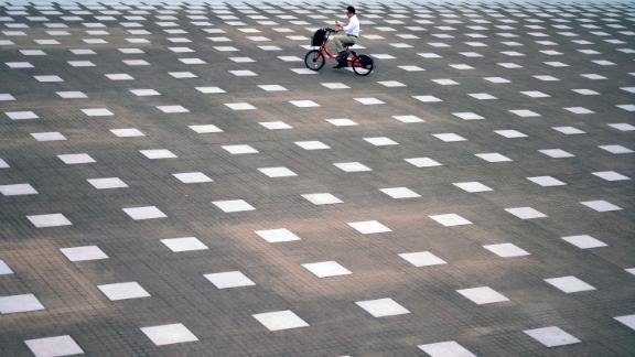 Yokohama, Japan: A man rides a public electric bike through the port city of Yokohama, Japan