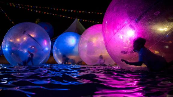Richmond, British Columbia: Children float inside inflatable water walking balls in a pool at the Richmond Night Market in the Canadian city of Richmond in August.