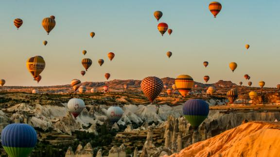 Cappadocia, Turkey: Hot-air balloons rise into the sky at sunset, allowing tourists stunning views of cone-shaped rock formations and rippled ravines.