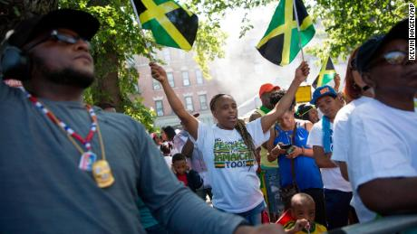 A spectator waves Jamaican flags during the West Indian Day Parade on Monday, Sept. 4, 2017, in the Brooklyn borough of New York. The parade, one of the largest celebrations of Caribbean culture in the U.S., is being held amid ramped-up security. (AP Photo/Kevin Hagen)