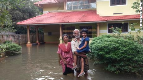 Idicula Gevarghese stands with his wife, Susamma Dikla, and granddaughter Shobita outside their flooded home in Venmony, Kerala.