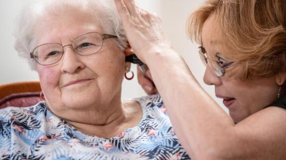 """Janie York examines the ear of Elaine Martin at the SilverRidge Assisted Living facility in Gretna, Neb., on Aug. 15, 2018. Martin had """"quite a bit"""" of earwax before getting her ears cleaned by York and getting hearing aids, at her daughter's urging. Now, York keeps Martin's ears clear with regular cleanings. (Chris Machian for KHN)"""