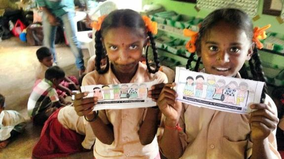 Girls from a Dark is Divine session holding their drawings to celebrate skin tone diversity in Tamil Nadu, India.