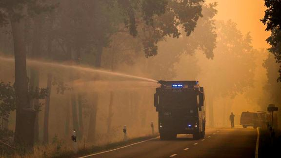 A police water cannon douses a forest near Treuenbrietzen Friday.