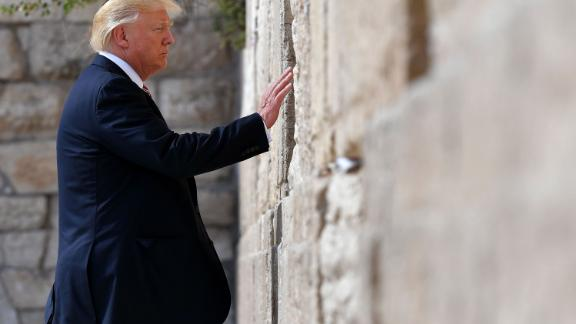 """Trump touches the Western Wall, Judaism's holiest prayer site, while in Jerusalem in May 2017. Trump became <a href=""""http://www.cnn.com/2017/05/22/politics/trump-israel-western-wall/"""" target=""""_blank"""">the first sitting US President to visit the wall.</a>"""