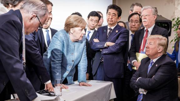 """In this photo provided by the German Government Press Office, German Chancellor Angela Merkel talks with a seated Trump as they are surrounded by other leaders at the G7 summit in Charlevoix, Quebec, in June 2018. According to two senior diplomatic sources, <a href=""""https://www.cnn.com/2018/06/11/politics/g7-photo/index.html"""" target=""""_blank"""">the photo was taken</a> when there was a difficult conversation taking place regarding the G7's communique and several issues the United States had leading up to it."""