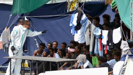 An official gestures towards migrants on the deck of the Italian Coast Guard ship Ubaldo Diciotti in the Sicilian port of Catania, on Thursday.