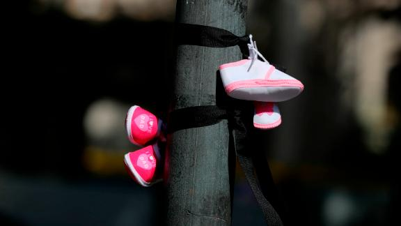 Protesters tie baby shoes to a post, signifying the children who died in mother and baby homes in Ireland, during a protest in Dublin ahead of the start of the Pope's visit to Ireland.