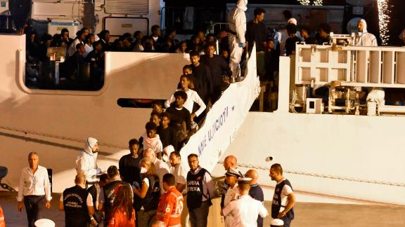 Migrants disembark an Italian Coast Guard ship in the port of Catania, Sicily, early Sunday morning.