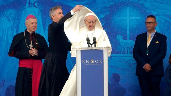An aide adjusts Pope Francis' cape as he speaks at the Knock Shrine in Knock, Ireland, on Sunday.