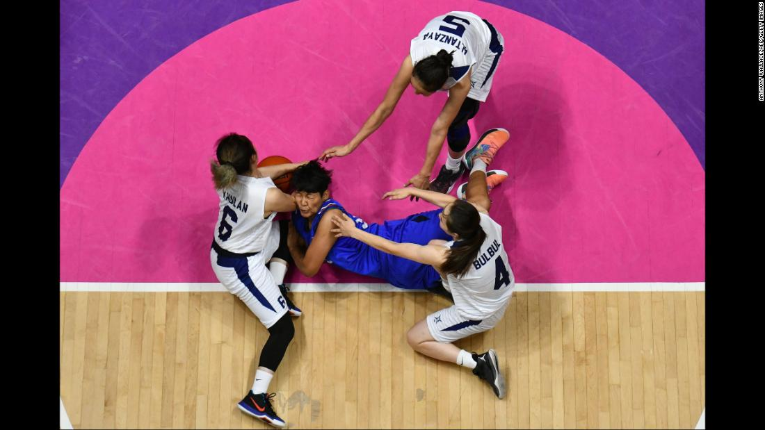 Thai basketball player Thidaporn Maihom is surrounded by Mongolian players during the Asian Games on Thursday, August 23.