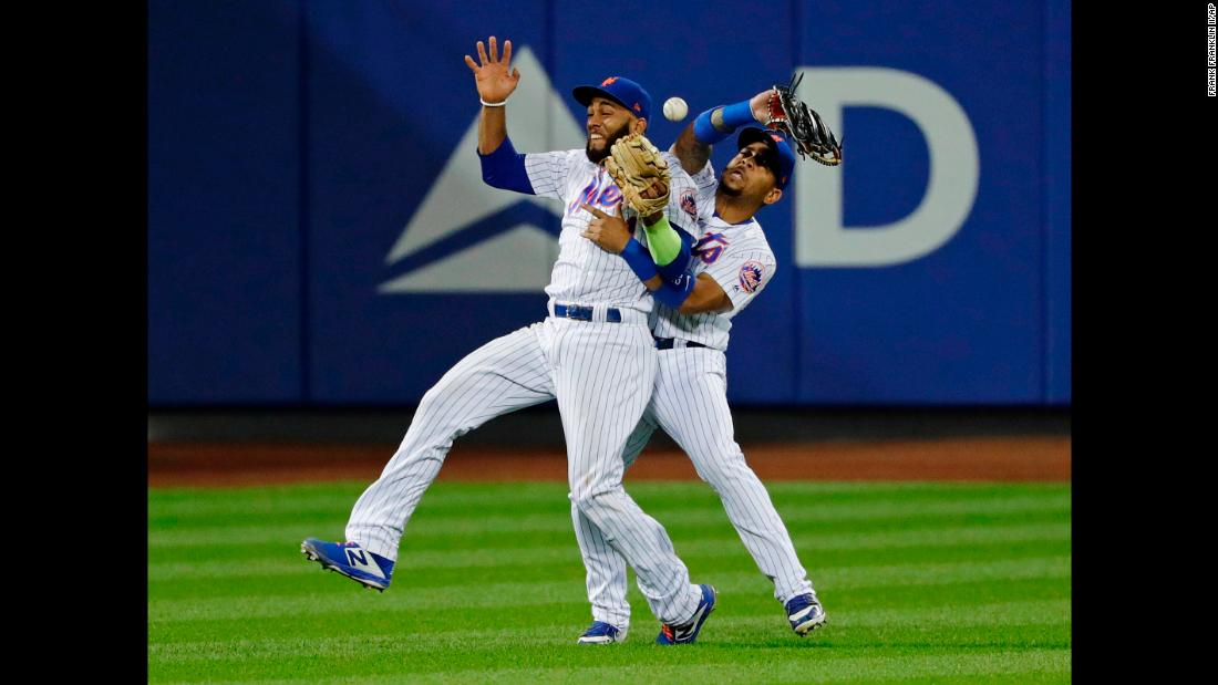 New York Mets teammates Amed Rosario, left, and Dominic Smith collide while trying to catch a pop fly on Monday, August 20. The collision came in the 13th inning and allowed San Francisco to score what proved to be the game-winning run.