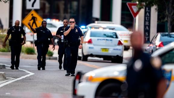 Police gather after an active shooter was reported at the Jacksonville Landing in Jacksonville, Fla., Sunday, Aug. 26, 2018. A gunman opened fire Sunday during an online video game tournament that was being livestreamed from a Florida mall, killing multiple people and sending many others to hospitals. (AP Photo/Laura Heald)