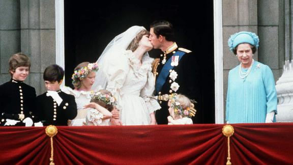 The Queen stands next to Prince Charles as he kisses his new bride, Princess Diana, on July 29, 1981.