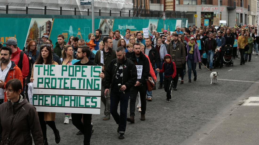 "Ailbhe O'Rourke and Fionn Dally hold a sign reading: ""The Pope is protecting paedophiles"" in protest over clerical sex abuse."