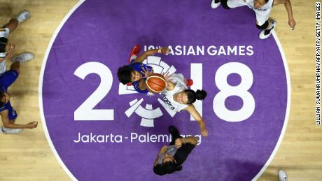 Unified Korea's Ro Suk Yong and Thailand's Kanokwan Prajuapsook go up for the jump ball during the women's basketball quarter-final match between Thailand and Unified Korea.