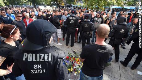 Riot police and citizens stand next to a makeshift memorial marking the site where three people were injured in a fight early Sunday. One man later died from his injuries, police said.