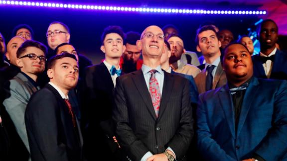 NBA Commissioner Adam Silver, center, poses for photographs with gamers at the NBA 2K League draft in April, 2018.